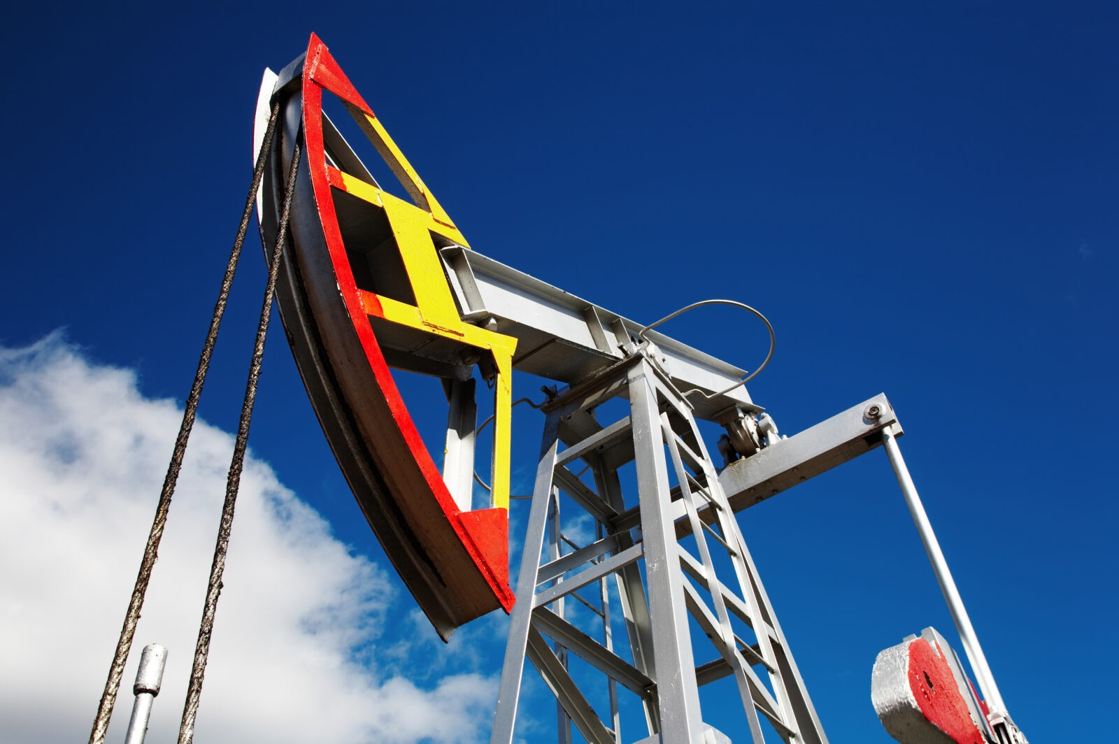 Oil pump jack against blue sky background