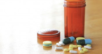 Many types of medicines on a wood table refers to health care.