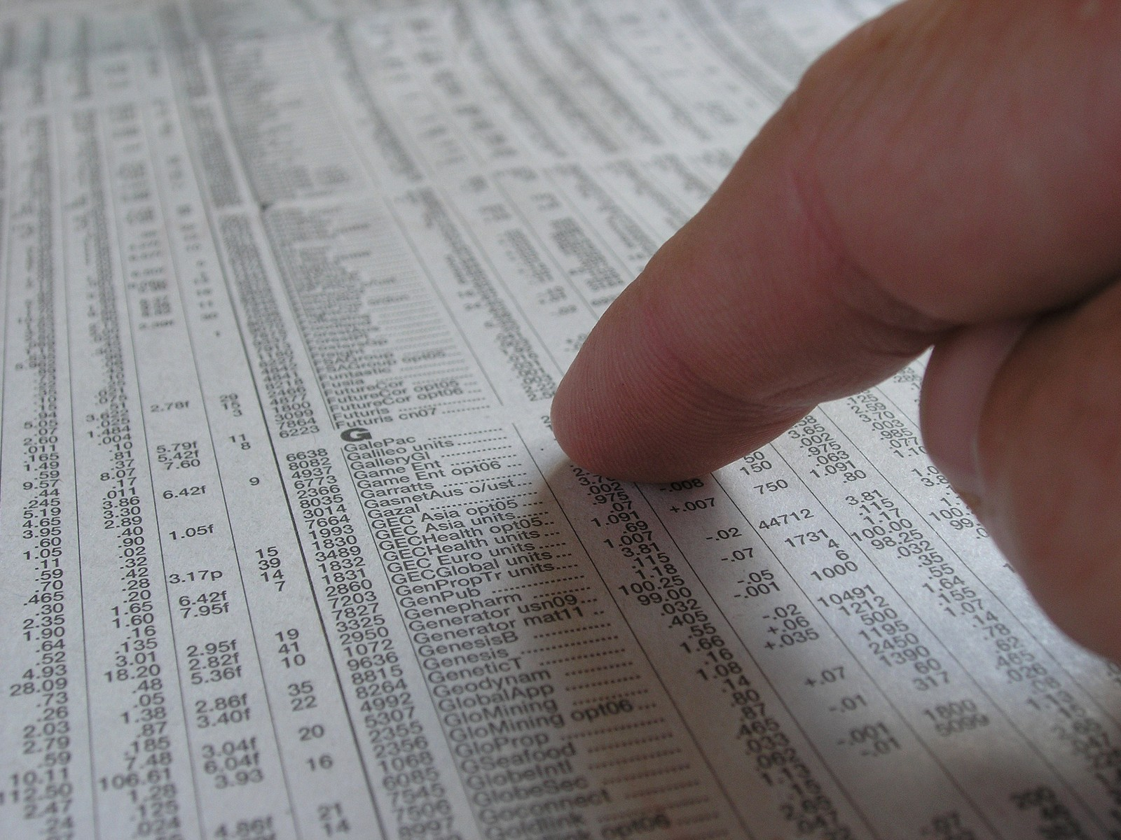 scanning stock prices on newspaper